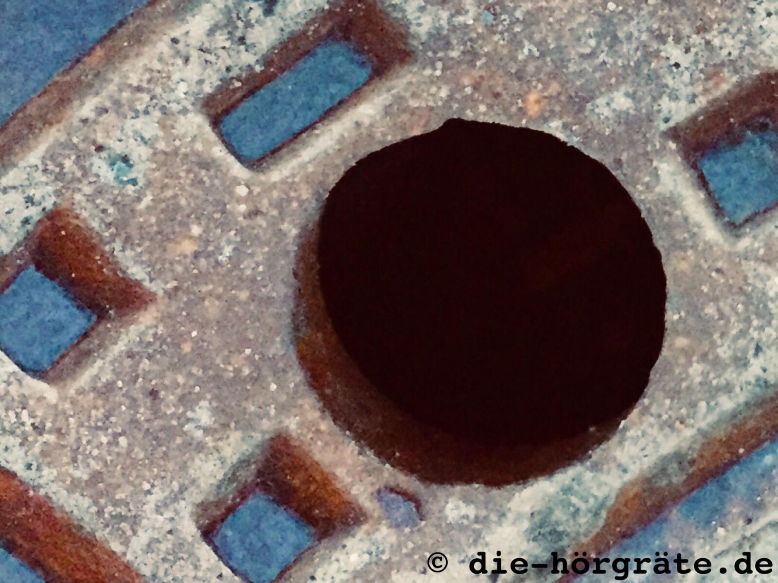 ein kleines Stück von einem alten, gusseisernen Kanaldeckel, vor allem ein Loch, durch das man ins Dunkel blicken kann