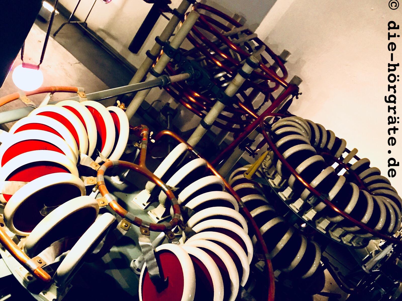 technische Dinge, runde, schöne rote Scheiben, die zu Kreisen angeordnet sind und ein bisschen wie die Räder von Kinderrollern aussehen, dazu schön glänzende Kupferrohre