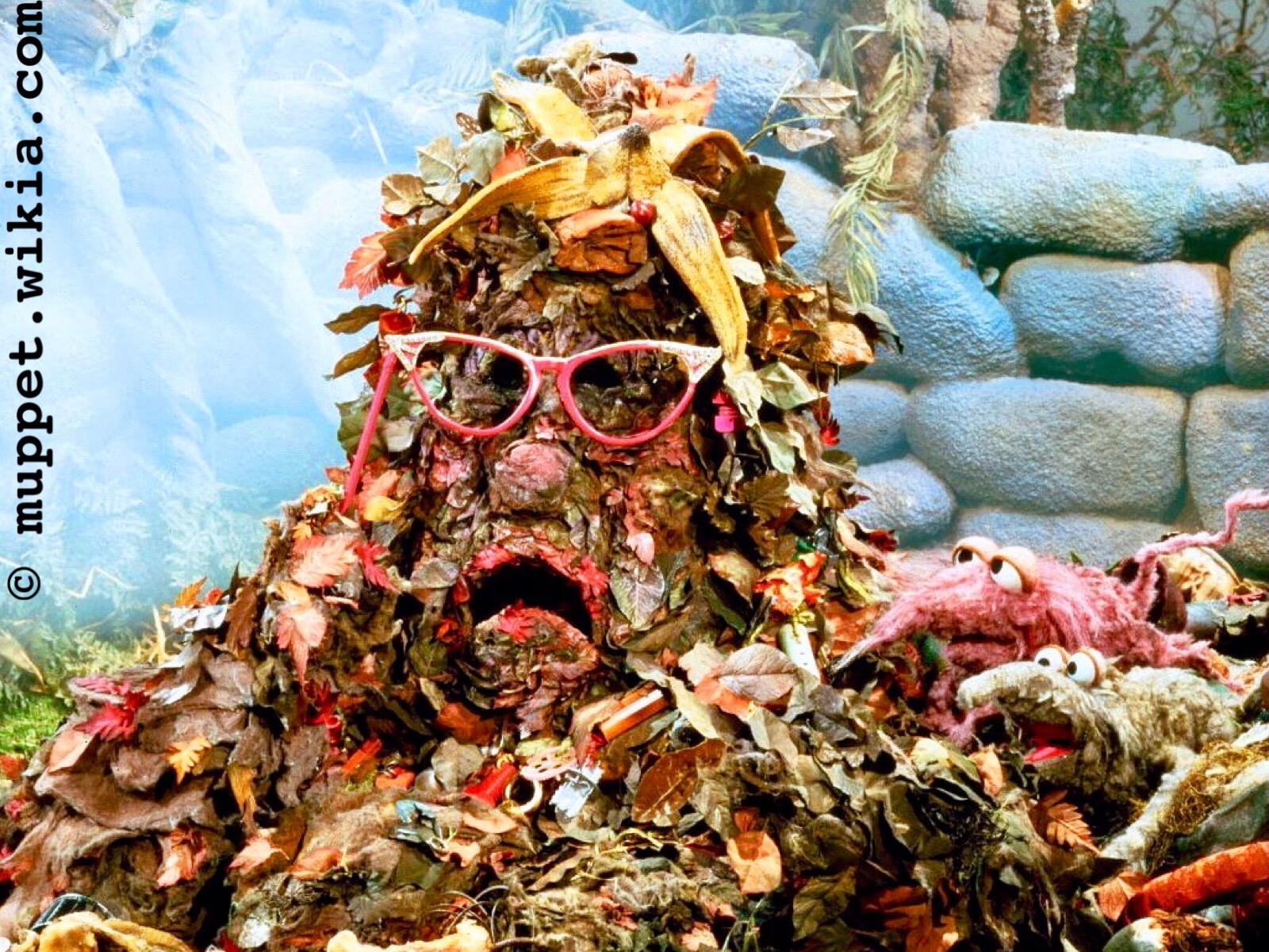 eine Puppe (für Puppenspiele), die eine Müllhalde ist - sie besteht aus ganz viel Laub, hat auf dem Kopf eine Bananenschale und eine schiefe, kaputte, rosa Plastik-Brille auf, sie spricht und ihre Mundwinkel zeigen nach unten