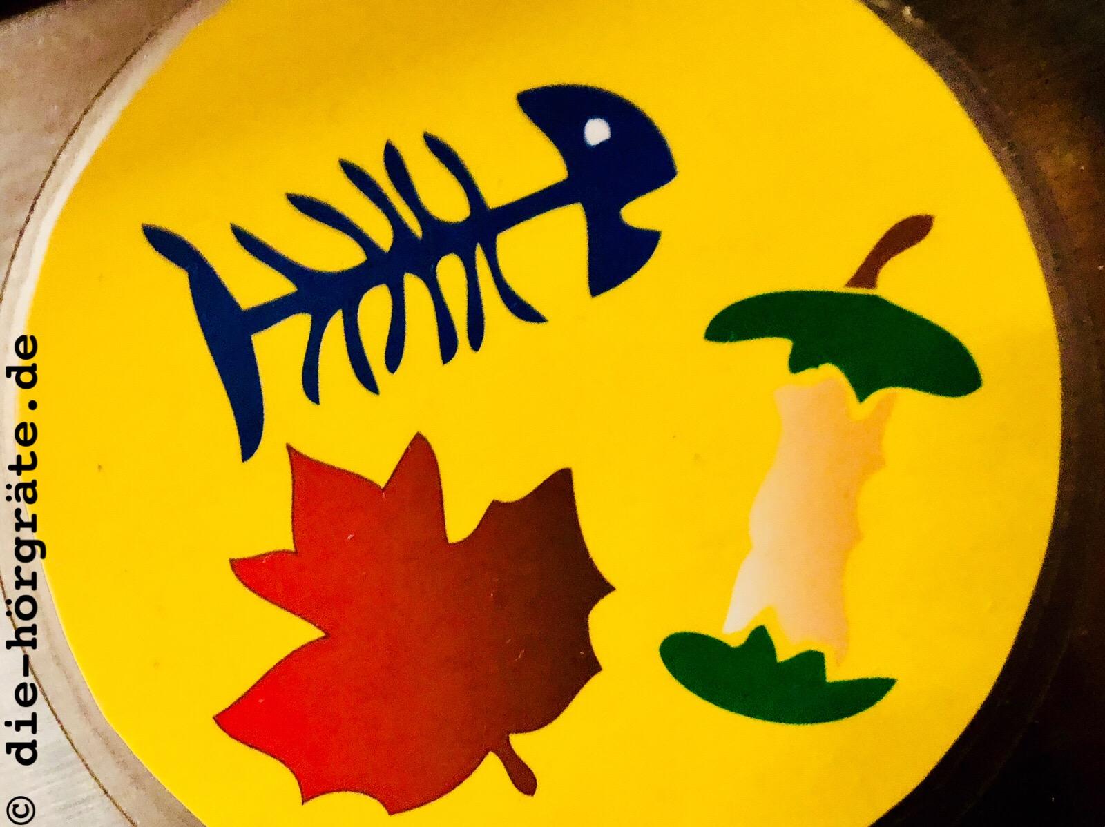ein runder, gelber Aufkleber auf einem Abfalleimer, darauf gezeichnet ein rotes Blatt, der Rest von einem Apfel und eine blaue Gräte