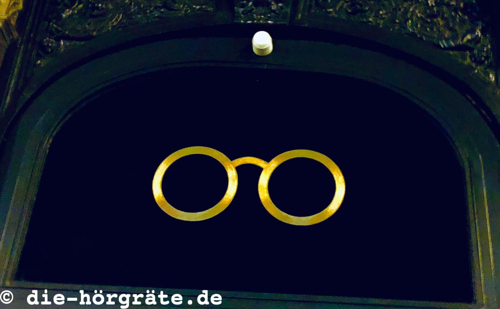 goldfarbene Brillenfassung über Optiker-Tür