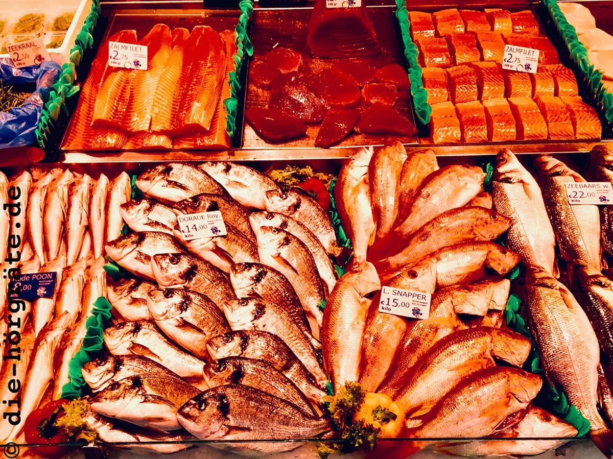eine Auslage mit verschiedenen, ordentlich drapierten Fischen bzw. Fisch-Stücken auf einem Markt, auf den Fischen liegen kleine Preisschilder