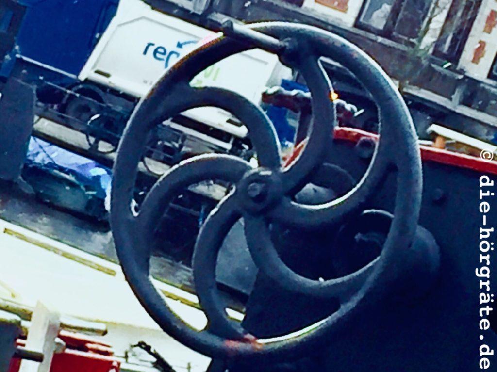 das schwarze Rad einer Ankerwinde auf einem Schiff, das Rad hat eine Kurbel und gebogene Speichen, im Hintergrund sind kleine Boote, Wasser, ein Steg