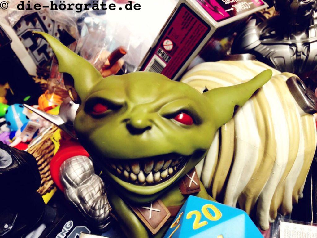 der Kopf von einer Gummifigur, die wie Yoda aussieht (grün und mit spitzen, großen Ohren) und zugleich sehr böse die Zähne fletscht