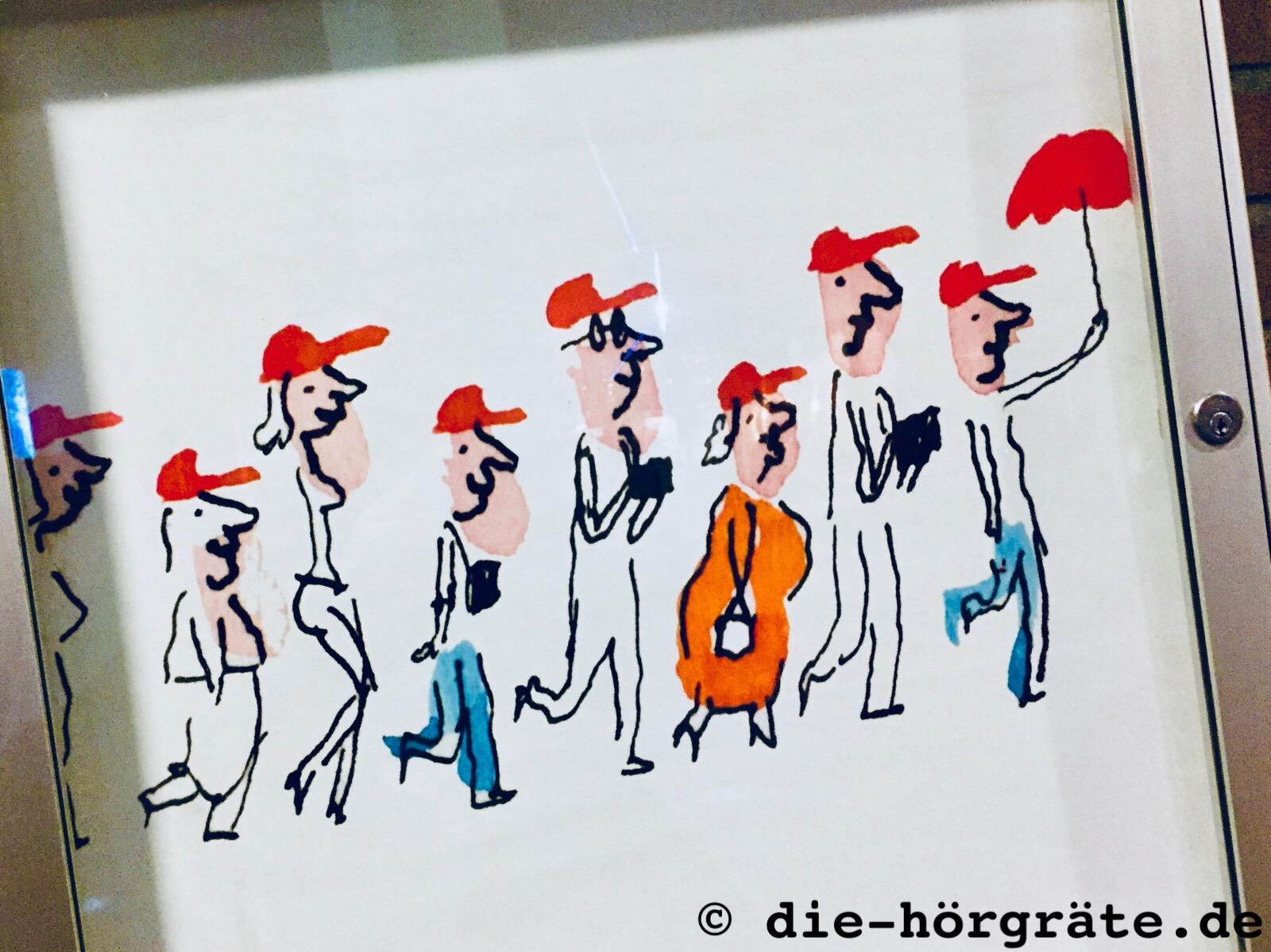Zeichnung von Leuten, die hintereinander laufen und alle rote Schirmmützen aufhaben, die Zeichnung hänt in einem Glaskasten