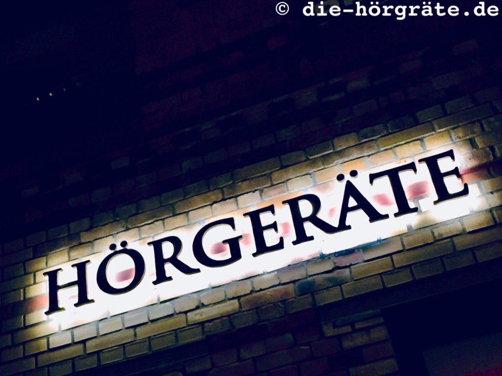 das Wort HÖRGERÄT aus metallenen Buchstaben vor einer Wand aus alten Ziegelsteinen, mit Licht angestrahlt