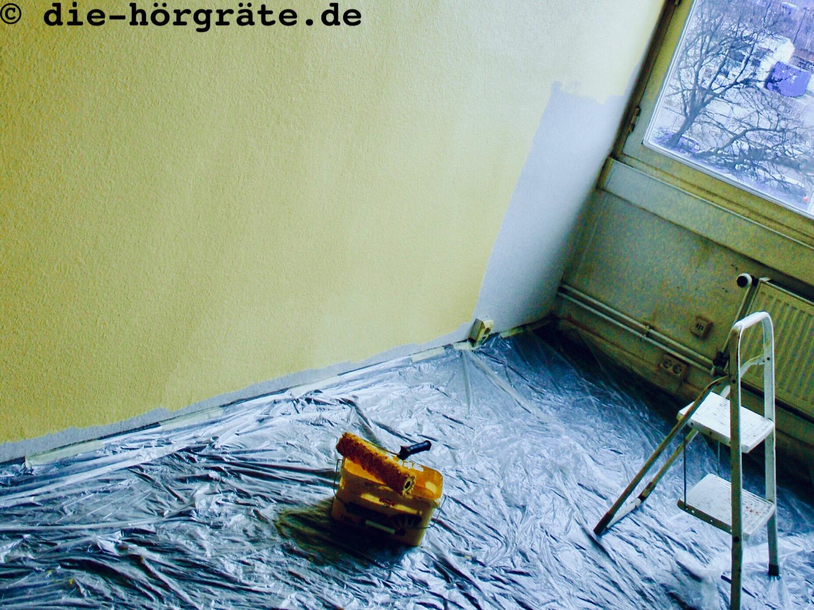 die Ecke eines Büroraumes, der gerade Maisgelb gestrichen wird, der Fußboden ist mit Folie ausgelegt, darauf ein Farbbehälter mit Malerrolle und eine Trittleiter, die Wand ist fast schon komplett maisgelb