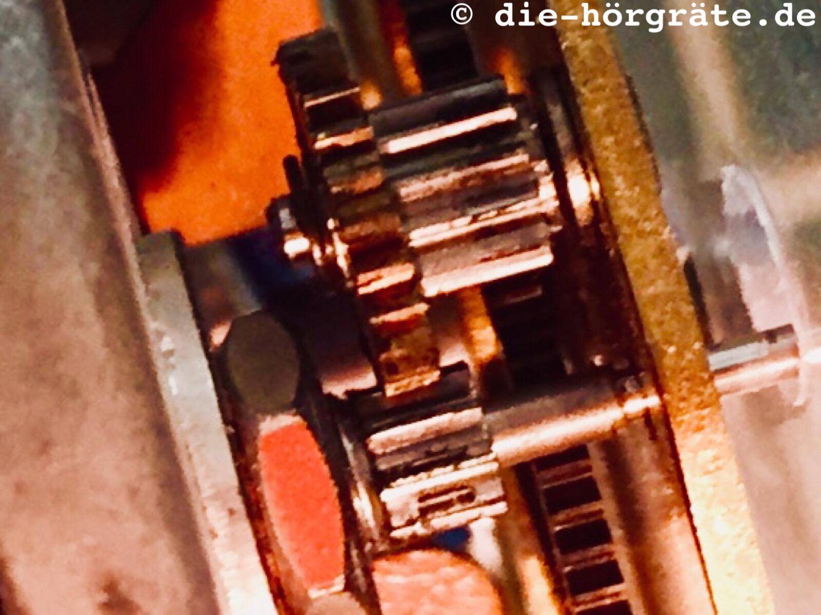 ein Click in ein Getriebe, in dem kleine Zahnräder ineinander greifen