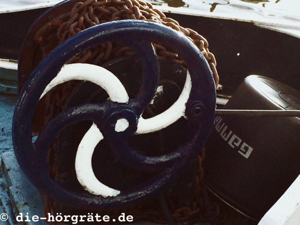 ein blau-weiß gestrichenes Rad einer Ankerwinde auf einem Schiff, auf der Winde ist eine rostige, schwere Metallkette aufgerollt
