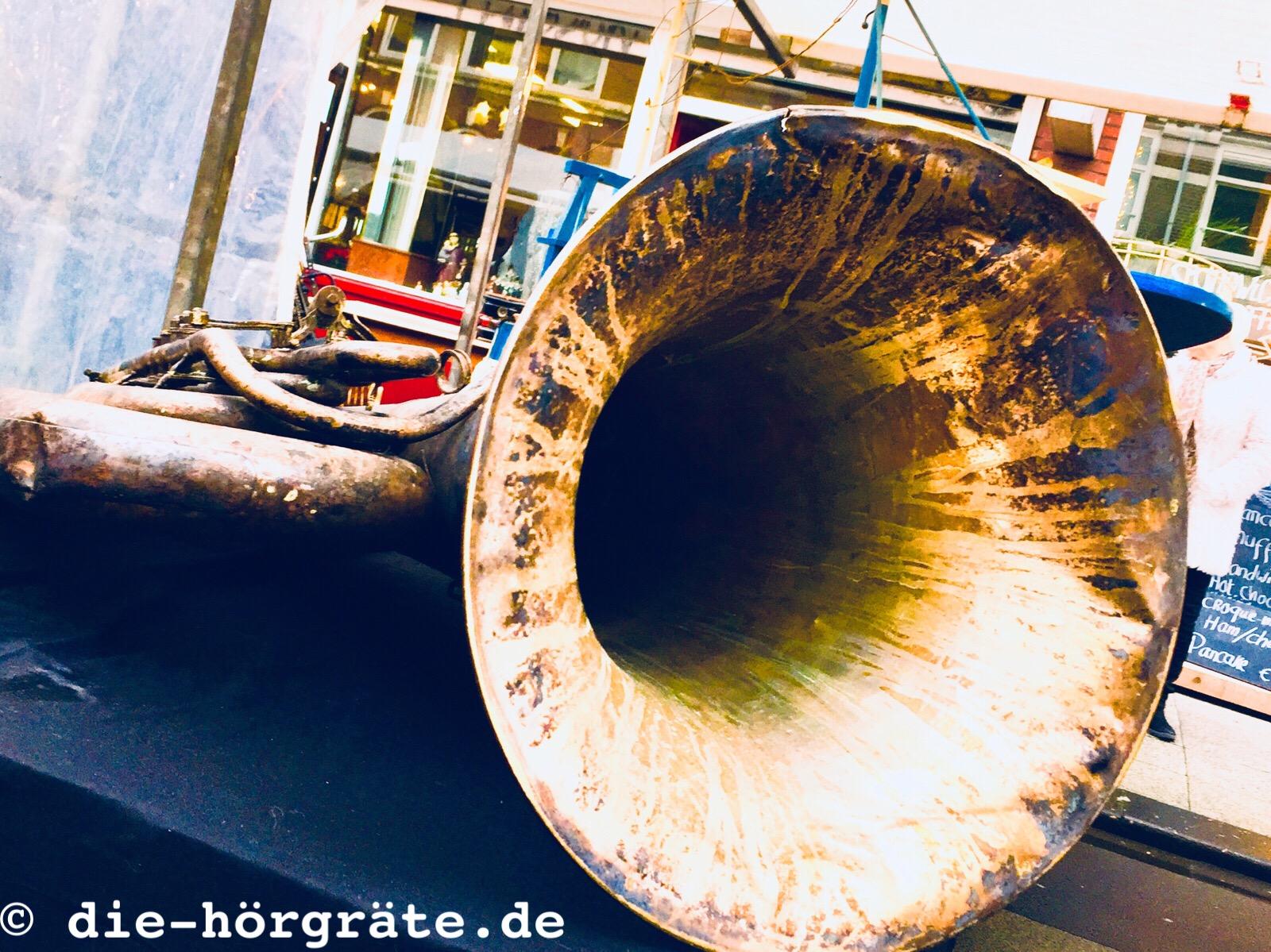 der Trichter einer alten Tuba auf dem Tisch auf einem Flohmarkt, die Tuba sieht ziemlich schmutzig aus