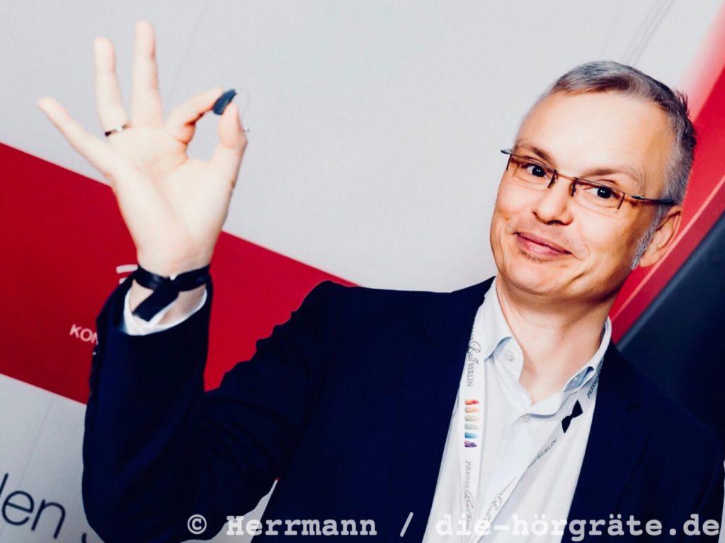 der Blog-Autor Martin Schaarschmidt lächelt in die Kamera und zeigt ein kleines Hörgerät, das er zwischen Daumen und Zeigefinger hält
