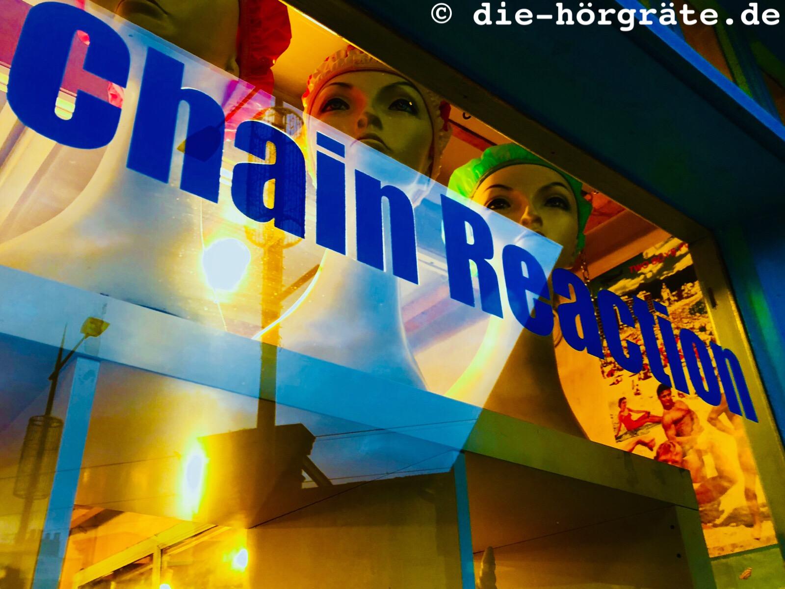 Blick in ein Schaufenster, in dem sich Licht spiegelt, dahinter stehen drei Kunstköpfe mit weiblichen Gesichtern und farbigen Duschhauben, auf der Fensterscheibe steht in blauen Buchstaben: Chain Reaction