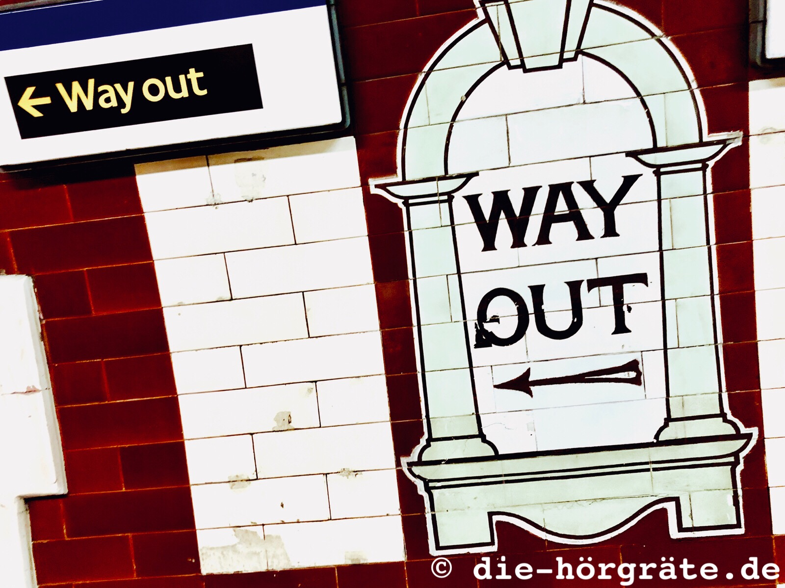 """ein modernes Schild mit der Aufschrift """"Way out"""" und ein altes Wandbild aus farbigen Fliesen, das eine Art Fensterbogen darstellt, darin steht ebenfalls """"WAY OUT"""""""