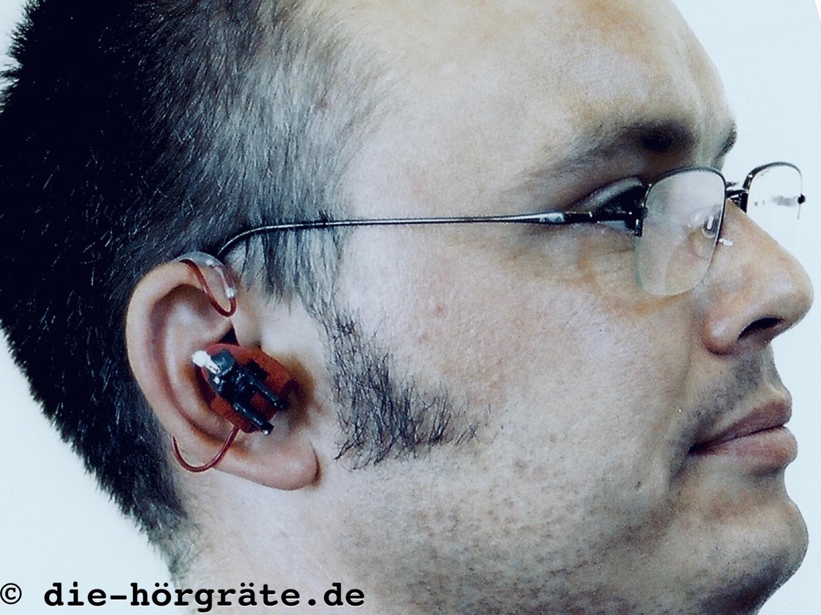 der Blog-Autor Martin Schaarschmidt mit einem gebastelten Politiker-Hörgerät - zu sehen ist der Kopf mit kurzen Haaren und Brille, im Ohr trägt er das Politiker-Hörgerät