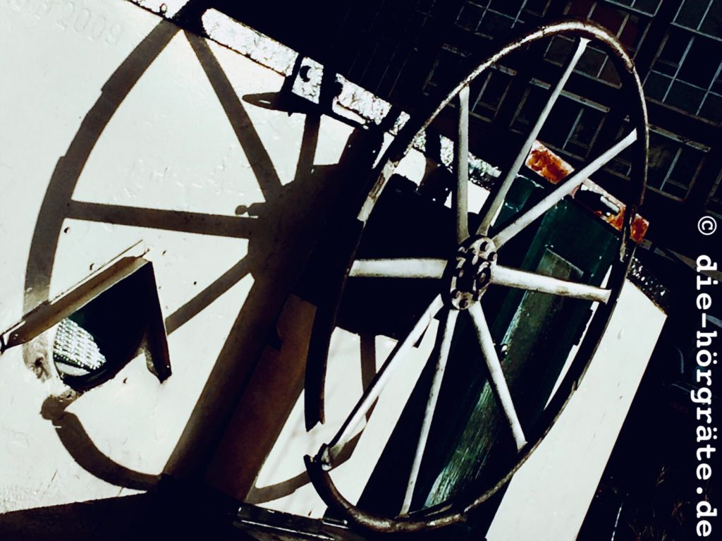 ein altes, eisernes Steuerrad von einem Frachtschiff, dahinter der Einstieg in die Kajüte des Schiffs und die Fenster einiger Häuser