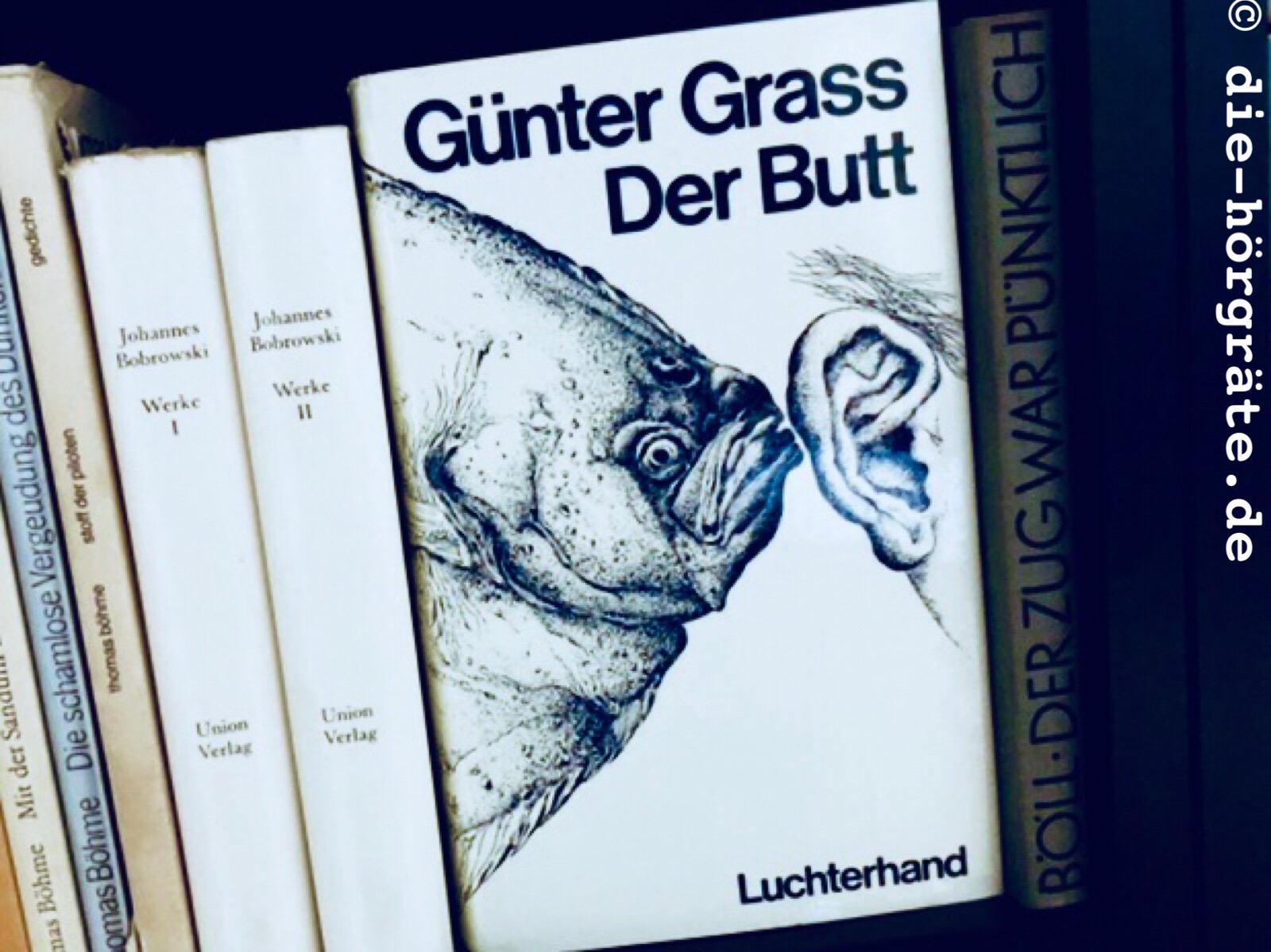 Ausschnitt aus einem Bücherregal, in dem ein Buchcover von vorne zu sehen ist: Günter Grass' Roman der Butt, auf dem Cover ist ein gezeichneter Butt und ein menschliches Ohr, in das der Butt zu sprechen scheint
